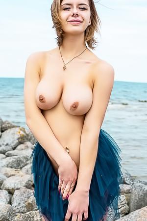 Belarusian brunette beauty Yelena wanders along a rocky shoreline