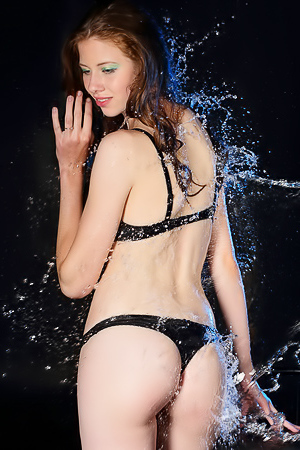 Dark-haired babe orgasms under streams of water.
